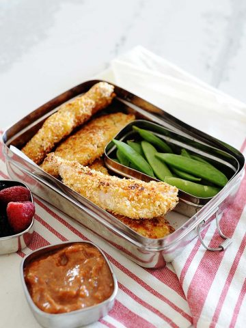 Images: baked chicken tenders and snap peas in a lunchbox with marinara in a sauce cup, on the side.