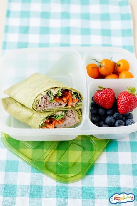 Image: overhead view of a turkey & Hummus veggie wrap in a lunch container with fruit and plantain chips.