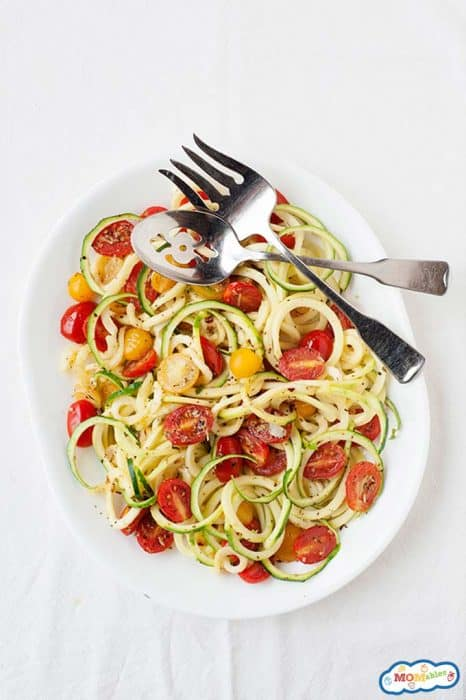 Image: overhead of a plate of zucchini and tomato pasta with serving forks