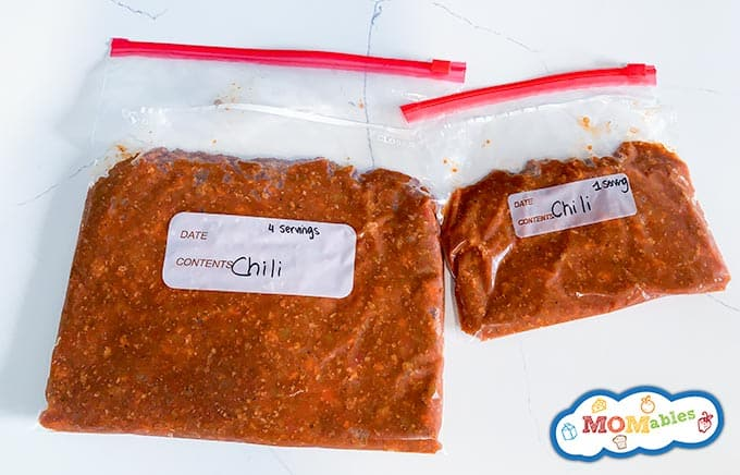 image: closeup two freezer zip bags filled with frozen chili. 1 large, 4 serving bag, 1 small, 1 serving bag.
