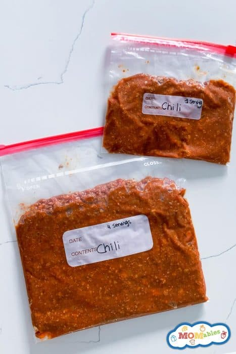 image: two bags zip bags of chili frozen flat and laid out on a counter top.