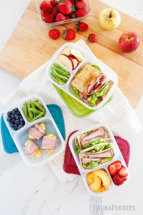 image: overhead view of three lunch containers packed with various school lunches including sandwiches, ham tacos, fruit, apple roll ups and more.