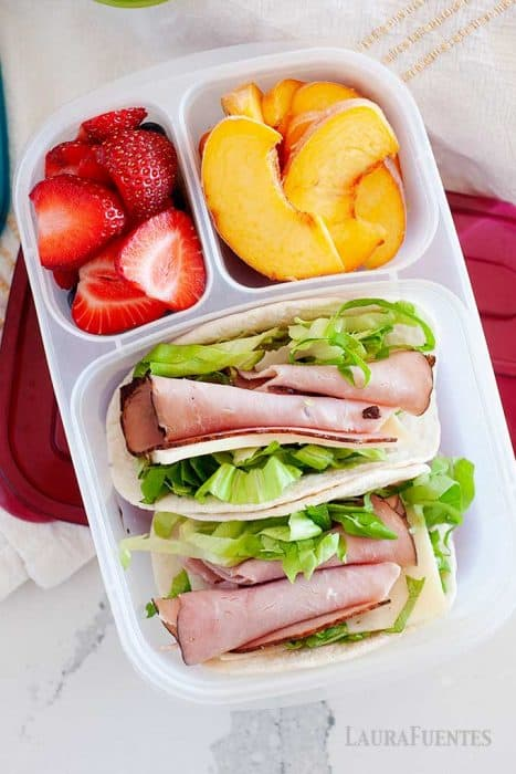 image: overhead view of a school lunch container filled with sliced ham tacos, strawberries and peach slices.
