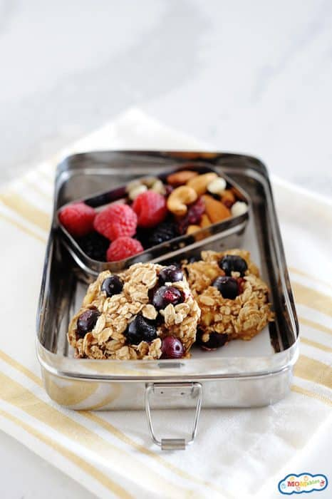 Image: blueberry oatmeal cookies in a tin lunchbox with fruit and nuts on the side.