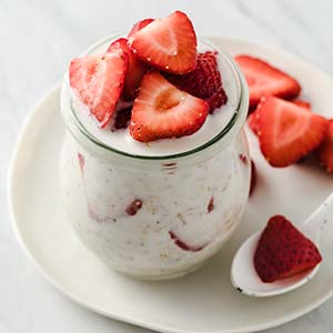 image: overhead view of overnight oats in a small jar and topped with strawberries