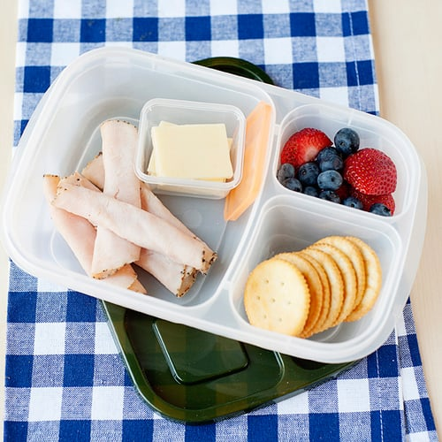 image: turkey roll ups with cheese slices, crackers and berries in a lunch container.