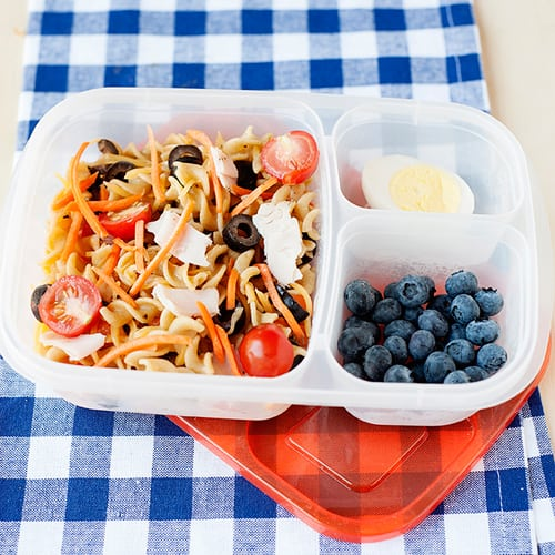 image: pasta salad with turkey pieces, tomatoes and sliced olives in a lunch container with blueberries and half a boiled egg.