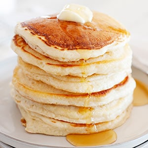 image: stack of pancakes cooked without eggs and topped with syrup and butter.