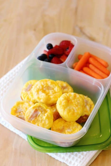 image: lunch container with 9 mini quiches, strawberries and carrot sticks.