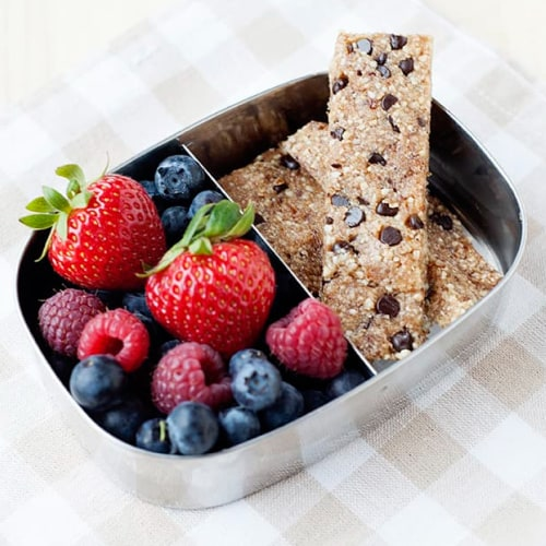two chocolate chip bars in a small lunch tin with berries