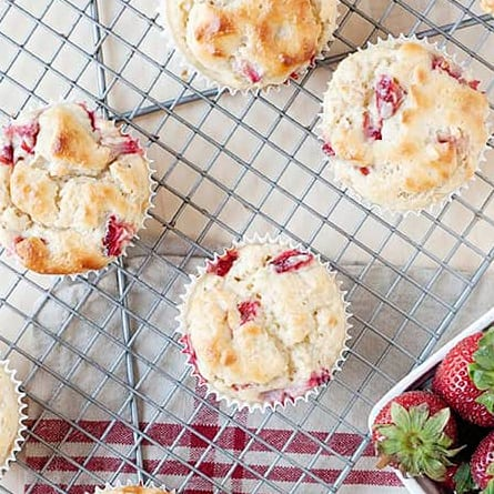image: four strawberry muffins on a cooling rack. Small box of strawberries in a corner.