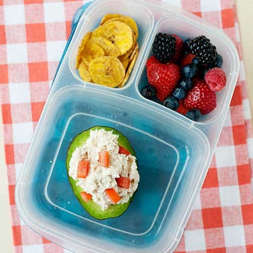 stuffed avocado in lunch container with berries and plantain chips