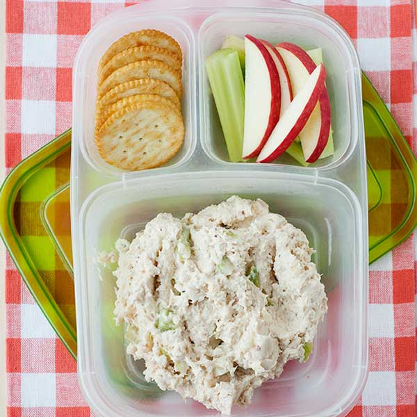 chicken salad in a lunch container with crackers and sliced fruit