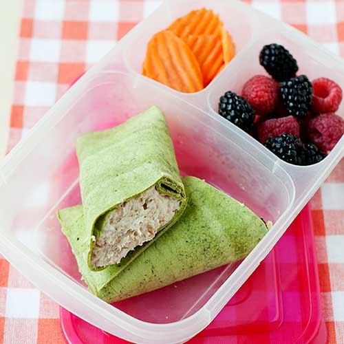 chicken salad wrap in a lunch container with sliced carrots and berries