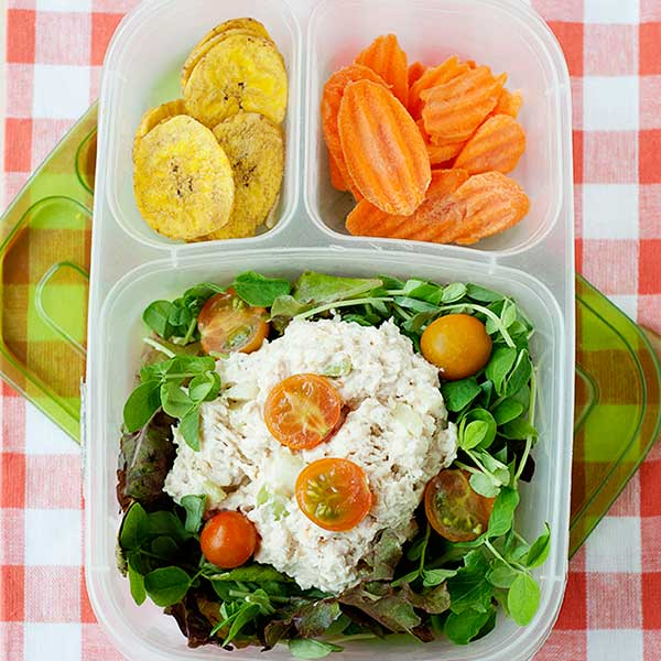 chicken salad on a bed of lettuce inside a lunch container