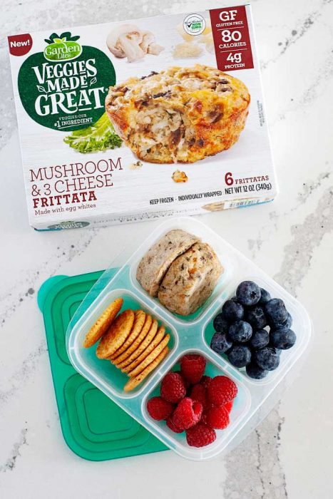lunchbox container with crackers, berries and frittata next to box of mushroom frittatas on countertop