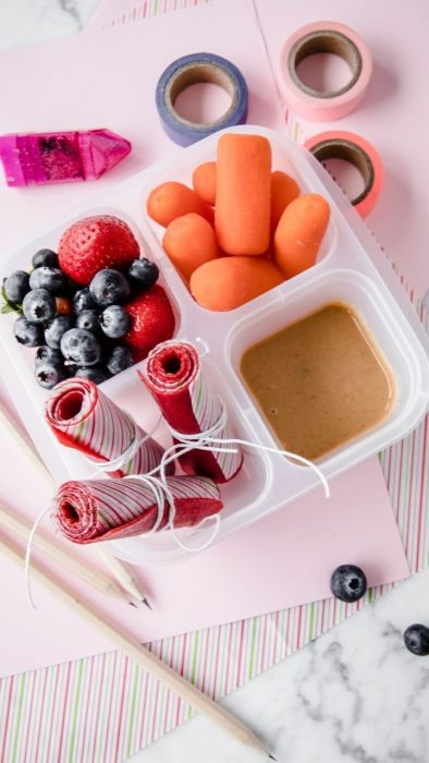 image: homemade fruit roll ups in a small lunch container along with berries, carrot sticks and veggie dip.