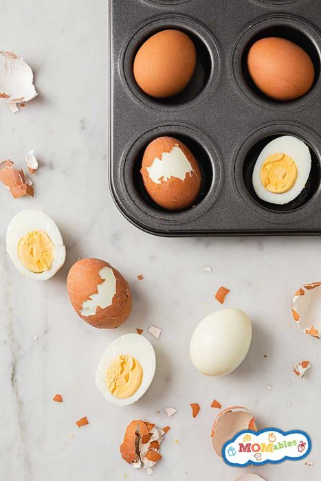 muffin tin with eggs in it. boiled eggs to the side in and out of shell