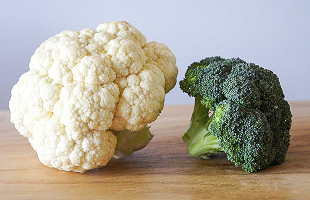 head of cauliflower and head of broccoli together on a countertop
